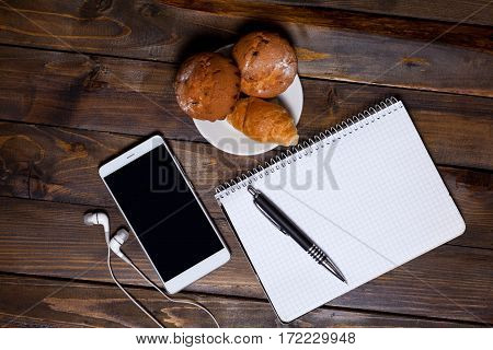 White Cup Of Coffee With Headphones And Mobile Phone And Lying Next To Notebook With Pen, Croissant