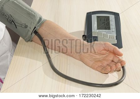 A person uses a device  for measuring arterial pressure
