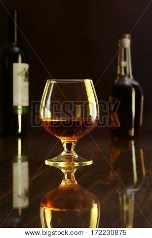 Glass of cognac, brandy or whiscy on black mirror table. bottles in a bar on the background.