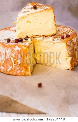 Close up of cut slice of French or German soft cheese with orange rind with mold creamy texture red pepper corns on parchment paper
