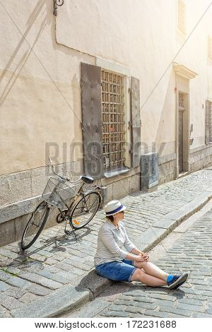 Young female traveler sitting with bicycle on the street in Stockholm Sweeden