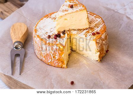 Top view of cut slice of French or German soft cheese with orange rind with mold creamy texture red pepper corns forkon parchment paper wood cutting board