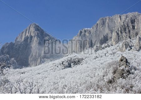 Winter landscape with rocks, snow and blue sky