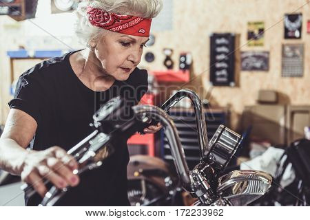 Calm old woman looking at speedometer of bike while standing near it in comfortable mechanic shop