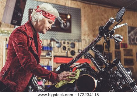 Cheerful old woman burnishing her bike in cozy mechanic shop