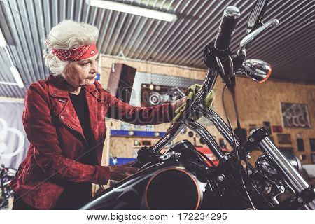 Pensive grandmother rubbing her motorcycle in comfortable garage