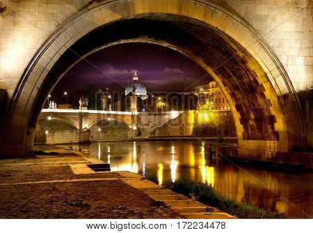 Night view on the Sant Angelo Bridge and Basilica of St. Peter in Rome, Italy
