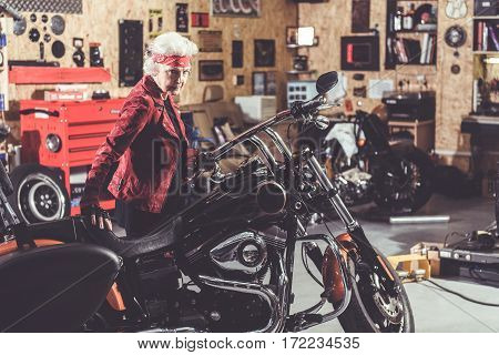 Earnest pensioner situating near her motorcycle in comfortable mechanic shop