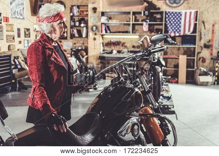 Calm old woman standing near motorcycle in wide cozy mechanic shop