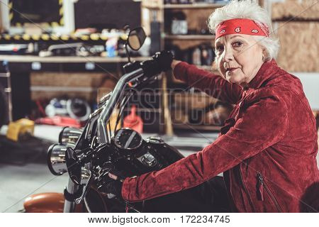 Cool grandmother sitting on bike while keeping heated grip in motor vehicle storage building