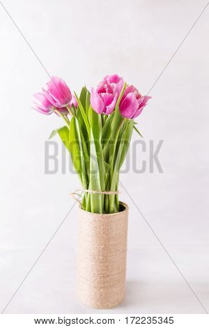 Pink tulips on a light background in handmade Vase. Pink tulip. Tulips. Flowers. Flower background. Flowers photo concept. Holidays photo concept. Copyspace