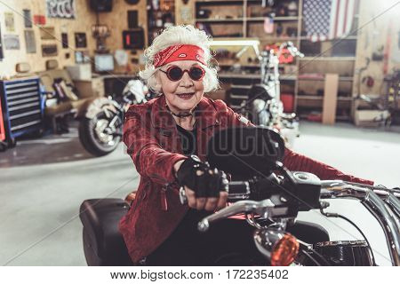 Cheerful old woman riding bike near shelves with tools in wide comfortable garage