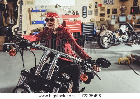Outgoing female retiree riding bike in wide comfortable garage with vehicle equipments inside it