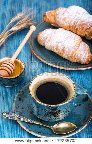 Crispy fresh croissant and hot espresso on blue background. Studio Photo