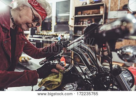 Smiling female pensioner polishing distance meter of motorcycle in mechanic shop