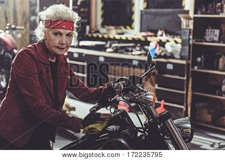 Calm grandmother cleaning bike near shelves with tools in mechanic shop
