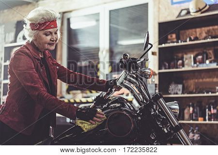 Cheerful female retiree rubbing motorcycle in comfortable mechanic shop