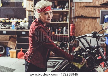 Outgoing old woman cleaning bike while standing near it in garage