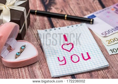 text i love you with gold earrings money on desk.