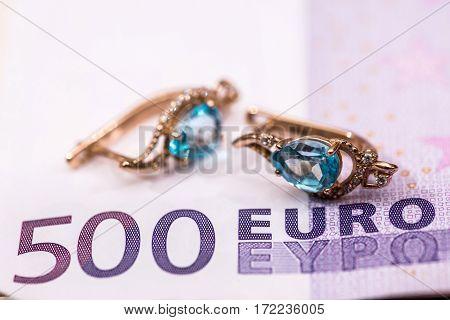 gold earrings lying on euros banknote .