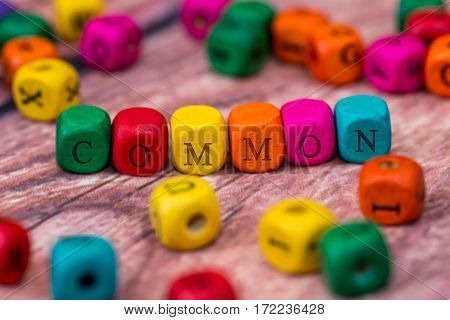 common - word created with colored wooden cubes on desk.