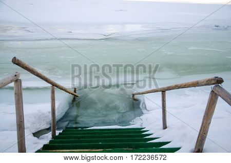 Ladder in hole ice water wooden railing