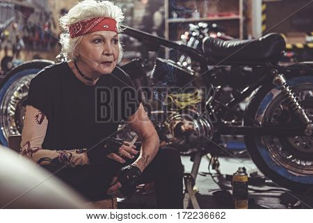 Serious old woman smoking while sitting on chair near bike in mechanic shop