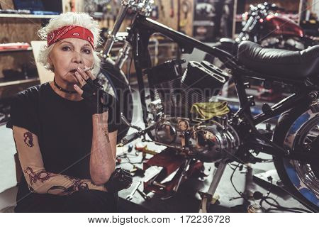 Pensive grandmother having cigarette while locating near motorcycle in garage