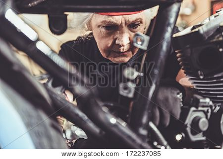 Focus on concentrated face of old woman making machine maintenance in garage