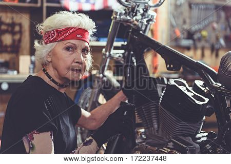 Thoughtful grandmother repairing bike while sitting next to it in comfortable garage