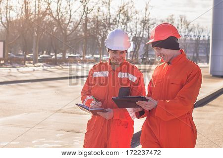 team of young engineers discussing project and writing in the note book. The wear overalls and safety helmets. Street background