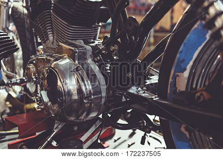close up motor of motorcycle situating in cozy mechanic shop for recondition vehicle