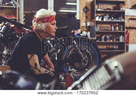 Pensive old woman reconditioning vehicle while situating near it in cozy mechanic shop