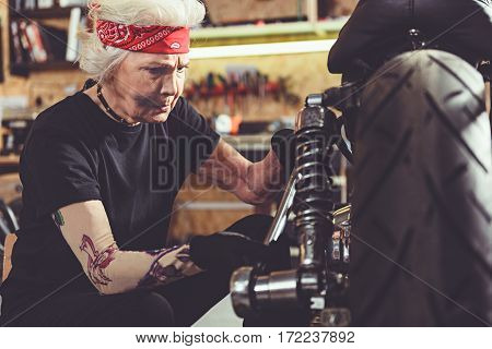 Cool old woman drawing bolts up tight on bike with screw key in garage