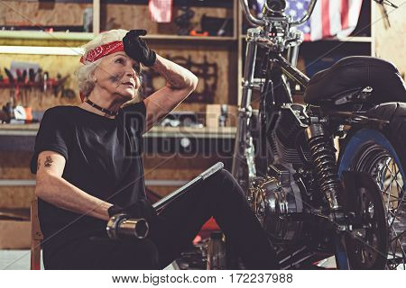 Calm tired grandmother sitting next to bike while repairing it in garage