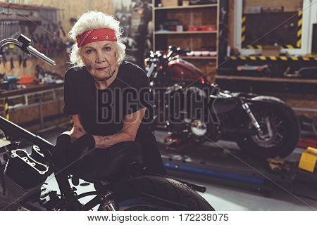 Calm grandmother situating near bike while bracing on it in garage