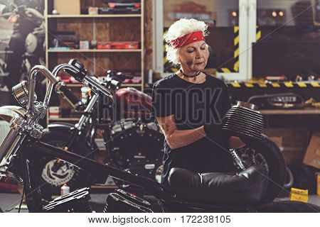 Thoughtful old woman reconditioning bike while standing next to it in comfortable mechanic shop
