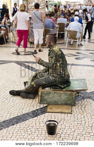LISBON, PORTUGAL - September 26, 2016: A street performer getting ready to play a living statue in the Rua Augusta street in downtown Lisbon Portugal