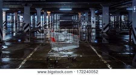 Abandoned and empty shopping trolley in the middle of the parking lot