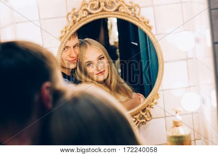 Loving couple hugging in the bathroom mirror. Lifestyle couples loving each other