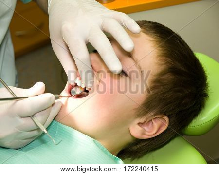 Young eight years old boy under dental preventional examination
