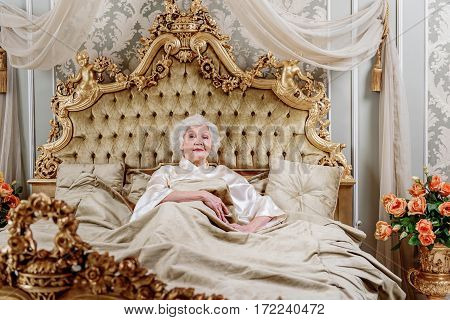 Rich mature lady is resting in chic bedroom. She is looking at camera with confidence