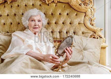 I have a lot of wrinkles. Pensive old woman is holding mirror and looking at camera with melancholy. She is lying on expensive bed
