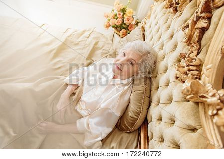 Calm old woman is relaxing in gorgeous bed. She is looking at camera with serenity