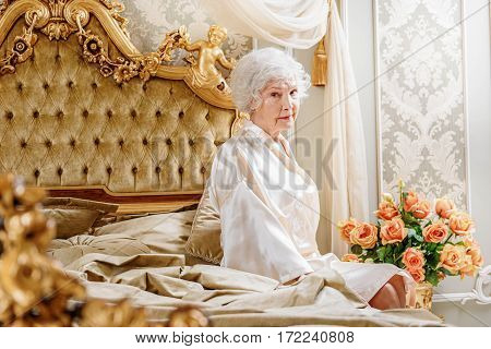 Upset mature woman is sitting on bed at home. She is looking forward with sadness