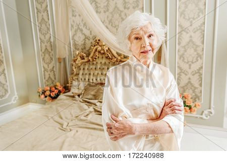 Kind old rich woman is standing near bed and smiling