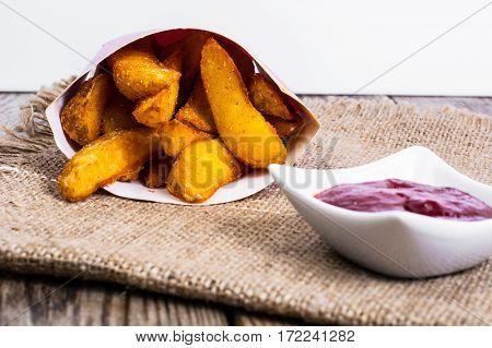 Potato wedges in rural on wood. Studio Photo