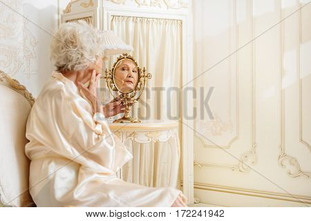 Old and lonely. Senior woman is looking at mirror while touching face with dissatisfaction