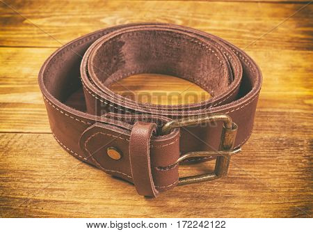 One man's leather belt on wooden table