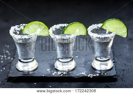 Set for tequila party with fresh lime slices and salt on black bar background